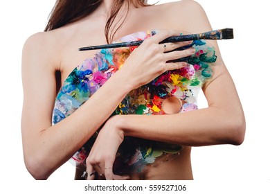 Nude thin attractive young female artist is holding hiding behind a color palette and brush, looking at camera. studio white background.