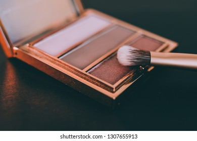 nude tones eyeshadows in a palette with brush and rose gold colors on dark background, concept of beauty and make-up trends