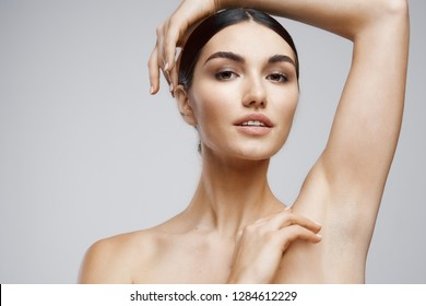 Nude woman with arm raised and underarm skin care