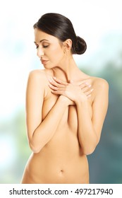 Nude woman crossing her arms on chest