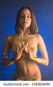 Nude woman with gold bodyart cropped shot