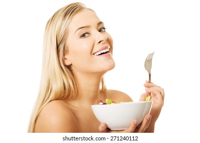 Nude woman holding a fork and bowl with salad.