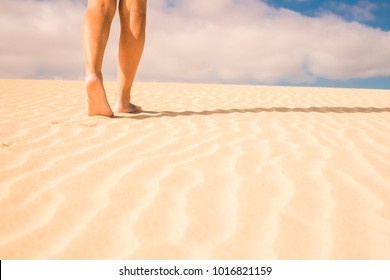 nude woman legs walking in the sand of the desert dunes of Corralejo, Fuerteventura. Nudism concept and summer time. Blue sky with clouds in background