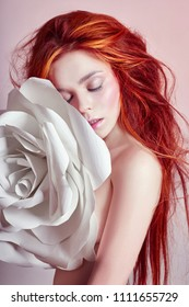 Nude woman with red hair hugs a big paper flower. Beautiful long hair girl, beautiful body. Artificial paper rose flower in the hands of a woman. Hair and body care, perfect skin