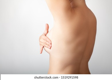 Nude woman self-examing breast. Breast cancer awarness
