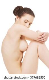 Nude woman sitting.