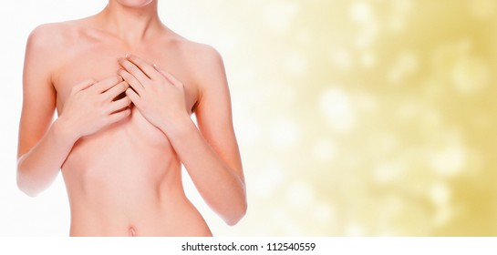 nude young female covering her breast with her hands, blurred pastel background