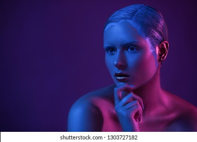 Nude Young Model with Creative Make Up in Beauty Shooting for Stock Agency on Dark Background in Blue Neon Light.