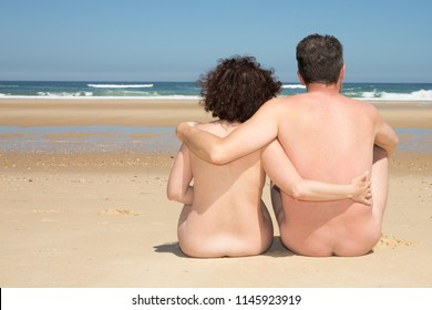 Nudism concept and summer time woman and man seen from behind relaxing on the seashore nudist beach