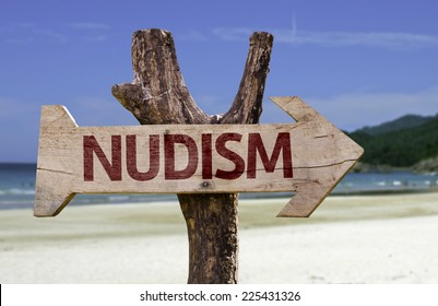 Nudism wooden sign with a beach on background