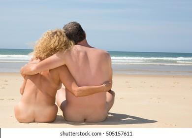 Nudist couple embracing on beach under deep blue sky
