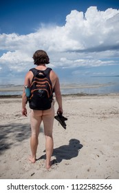 a nudist, wearing a backpack, is on vacation.