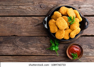 Nuggets. Chicken nuggets with ketchup on wooden table. Fast food