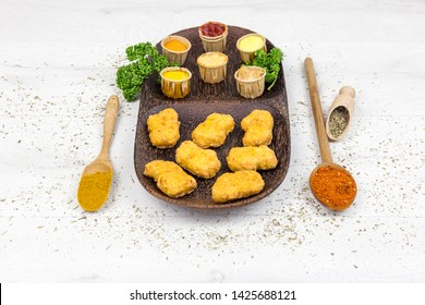 Nuggets chicken served with several sauces, with curcuma and red spice, served on a wooden plate.