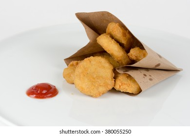 Nuggets in a paper bag with ketchup isolated on white