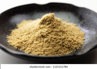 Nuka powder.  Mound or heap of Nuka on a black plate, used in making nukadoko, which is a rice bran for making Japanese fermentation or pickling of vegetables.