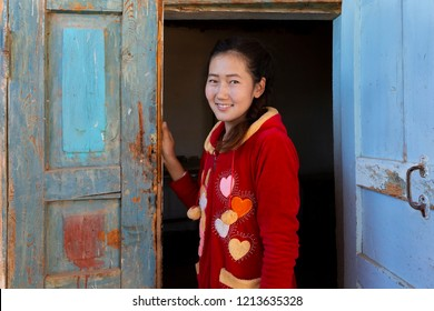 NUKUS, UZBEKISTAN - OCTOBER18, 2018: Central asian girl smiles and looks at me through wooden doors, in Nukus, Uzbekistan.