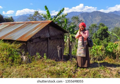 Num, Sankhuwasabha District, Nepal  - 11/17/2017 : Nepalese woman in traditional clothes greeting namaste with hands together like a prayer, next to her small house with tin roof.