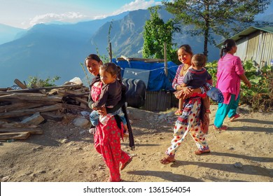Num, Sankhuwasabha District, Nepal - 11/17/2017: Two Nepalese women in colorful clothes carry their child while walking outside in a small mountain village in East-Nepal