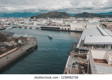 Numazu, Japan - April 12, 2017: High angle view of the port in Numazu Fish Market district with City of Numazu in the background on a Cloudy day