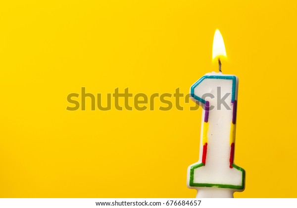 Number 1 birthday celebration candle against a bright yellow background