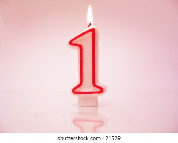 A Number 1 Candle Lit Against Pink Background