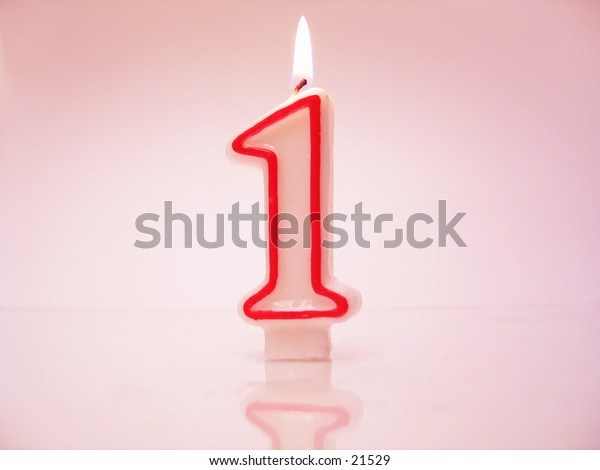 A number 1 candle lit against pink background.