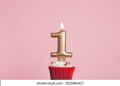 Number 1 gold candle in a cupcake against a pastel pink background