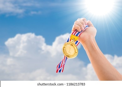 Number 1 winner holding medal gold award to sky.