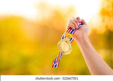 Ganador número 1 sosteniendo el premio de medalla de oro al cielo.