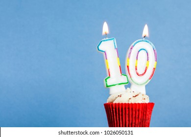 Number 10 Birthday Candle In A Cupcake Against Blue Background