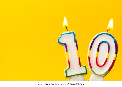 Number 10 birthday celebration candle against a bright yellow background