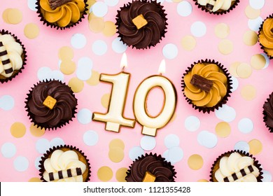 Number 10 gold candle with cupcakes against a pastel pink background