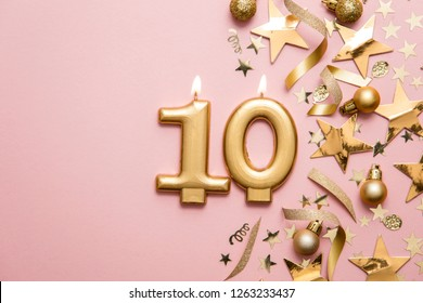 Number 10 gold celebration candle on star and glitter background