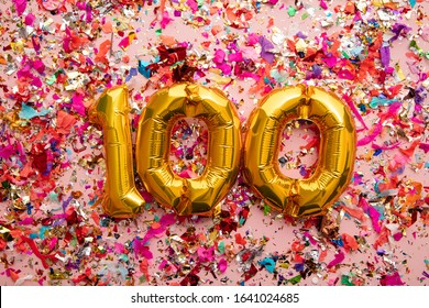 Number 100 gold birthday celebration balloon on a confetti glitter background