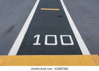 """Number """" 100 """"  on white and yellow runway. Takeoff runway and runway aircraft carrier on battleship. Public area."""