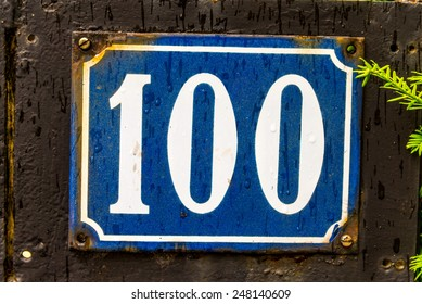The number 100 street address sign with white characters and a blue background.