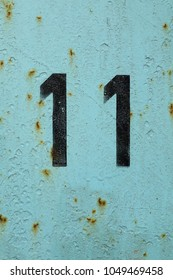 number 11, black stencil numbers on blue background, eleven