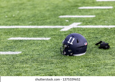 Number 11 of a football helmet and a pair of white gloves are laying on the grass