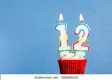 Number 12 Birthday Candle In A Cupcake Against Blue Background