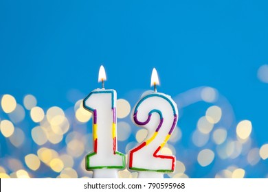 Number 12 Birthday Celebration Candle Against A Bright Lights And Blue Background
