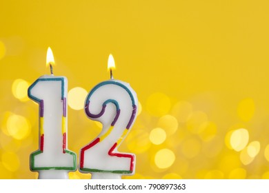 Number 12 Birthday Celebration Candle Against A Bright Lights And Yellow Background