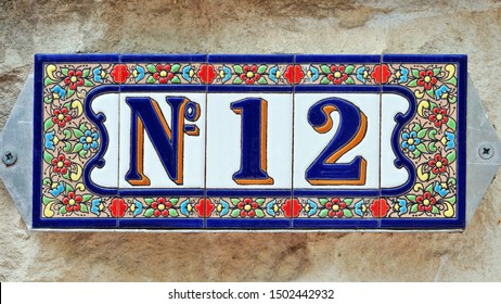 Number 12, twelve, house number decorative ceramic tile digit on a grunge stone wall.