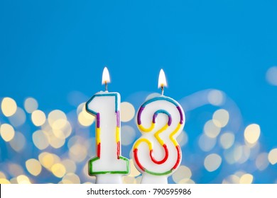 Number 13 birthday celebration candle against a bright lights and blue background