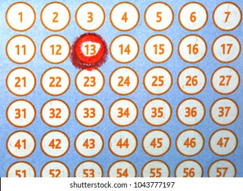 The number 13 circled in red in a lottery bingo card
