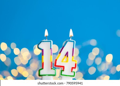 Number 14 birthday celebration candle against a bright lights and blue background