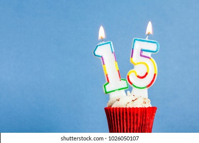 Number 15 birthday candle in a cupcake against a blue background