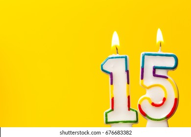 Number 15 Birthday Celebration Candle Against A Bright Yellow Background
