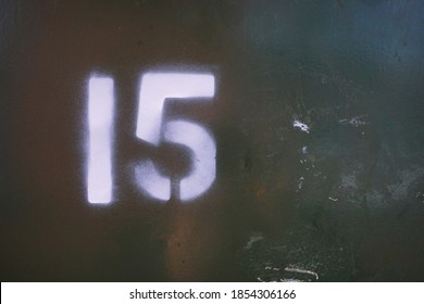 Number 15 / fifteen spraypainted in an urban graffiti stencil style  on distressed green grime metallic background