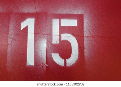 number 15, white stencil letters on red background